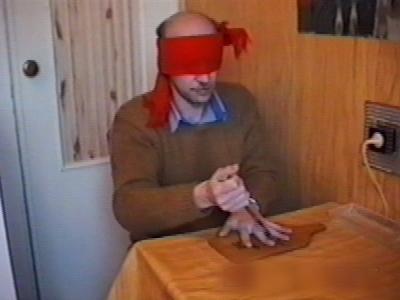 Blindfolded man stabs between fingers