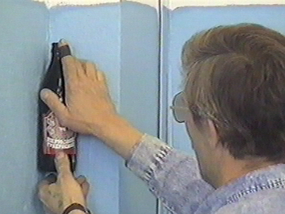 Man sticks bottle in corner of 2 walls