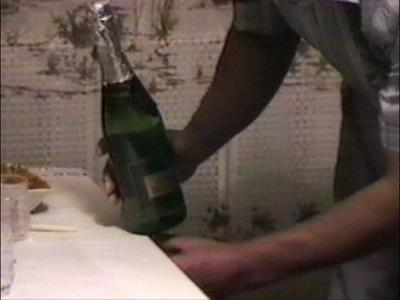 Man balancing bottles on edge of table