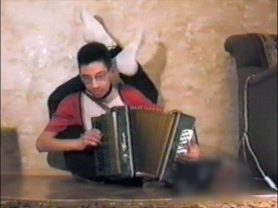 Man playing accordion- legs around neck