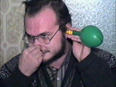 Man blowing up balloon using ear