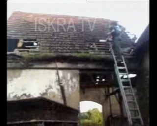 man uses chainsaw to demolish a roof