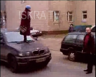 woman stands on car and shouts at man