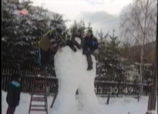 men falling off a tall snowman