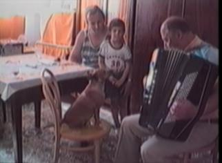 dog howls as man plays accordion