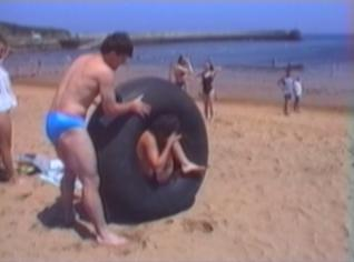 woman spins inside a tyre on beach