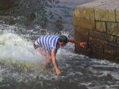 Man's trunks fall down as he tries to swim up the stream