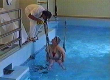 Therapist falls into pool as he lowers patient