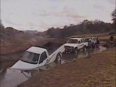A pickup truck drives in to deep water