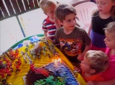 boy blowing another boy's birthday cake