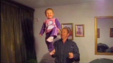 man balancing toddler on one hand
