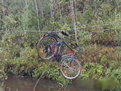 Kids hoist bike over bridge into river
