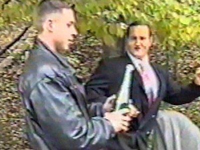 Man kicks man holding champagne, bottle pops