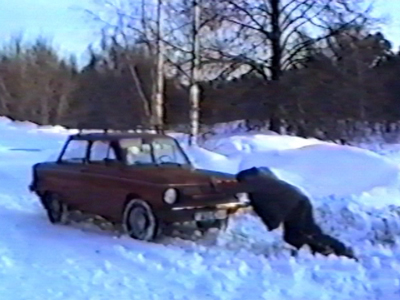Man pushes car backwards in snow, it runs away
